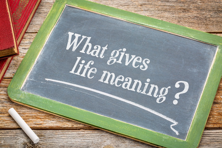 meaning: What gives life meaning question - a philosofical question on a slate blackboard with a white chalk and a stack of books against rustic wooden table