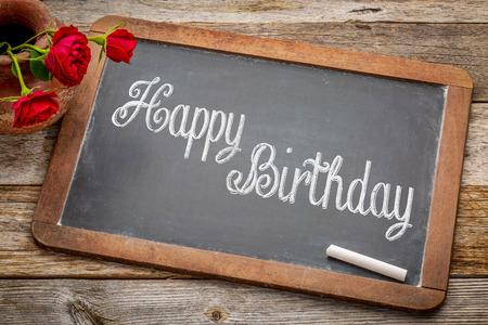 felicitaciones cumpleaÑos: Felices saludos de cumpleaños - texto blanco tiza en una pizarra pizarra de la vendimia con las rosas rojas contra la madera rústica