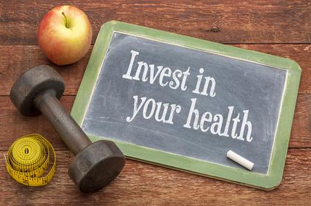 fitnes: Zainwestuj w swoje zdrowie - tablica łupek czerwony znak przed wyblakły malowane drewno stodoła z hantle, jabłka i centymetrem