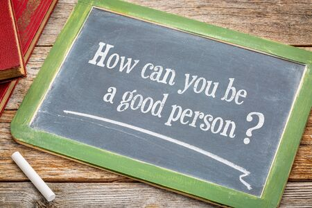 morale: How can you be a good person? An inspirational question on a  blackboard with a white chalk and books against rustic wooden table