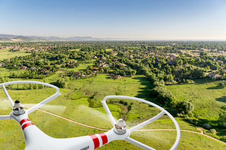 quadcopter drone flying over prairie landscape with city residential area in distance - digital composite image
