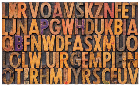 letterpress letters: background of vintage letterpress wood type printing blocks, random letters of alphabet and punctuation stained by color inks, isolated on white
