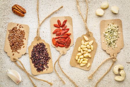 a vriety of superfood (nuts, berries, grain, seed) on paper price tags against grunge barn wood background Stok Fotoğraf