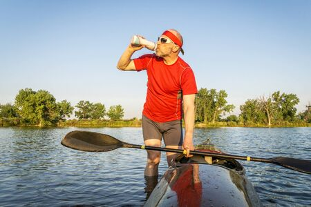 paddler: senior kayak paddler drinking water or sport drink after paddling workout on a lake in summer Stock Photo