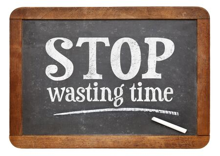 Stop wasting time sign - white chalk text on a vintage slate blackboard Imagens