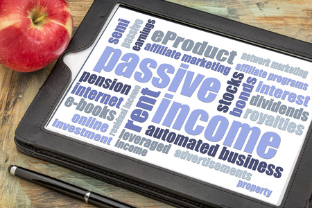 passive income: passive income word cloud  on a digital tablet with a red apple
