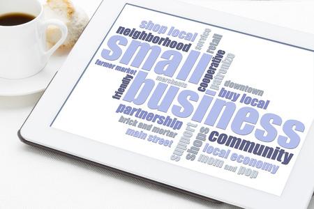 コーヒーのカップを持つデジタル タブレットのスモール ビジネス単語の雲