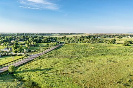aerial view: Aerial view of Rocky Mountains foothills near Fort Collins, Colorado with a green prairie, residential area and cyclist on a road Stock Photo