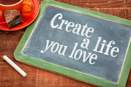 healthy life: Create life you love motivational advice - text  on a slate blackboard with chalk and cup of tea Stock Photo