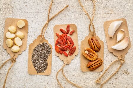 superfood: superfood abstract with price tags against  rustic barn wood (macadamia and pecan nuts, goji berries, chia seeds and garlic cloves) - healthy eating concept