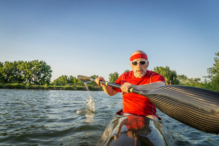 paddler: senior male paddler training in a racing sea kayak with a wing paddle on a lake, motion blur of paddle