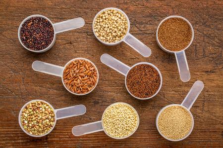 gluten free grains (quinoa, brown rice, kaniwa, amaranth, sorghum, millet, buckwheat, teff) - a set of measuring scoops on a rustic wood Stockfoto