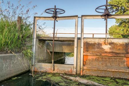 verjas: puertas (headgates) y el puente del pie de zanja de riego, verano en Colorado tierras de cultivo