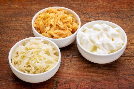 yaourts: la choucroute, le kimchi et le yaourt - aliment probiotique fermenté populaire - trois bol en céramique contre le bois rustique