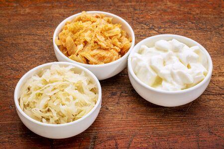 sauerkraut, kimchi and yogurt - popular probiotic fermented food - three ceramic bowl against rustic wood Stock Photo