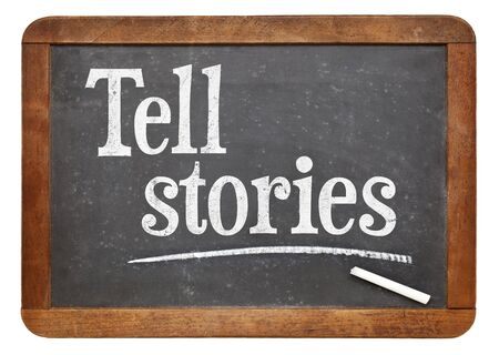 tell: Tell stories advice - text in white chalk on a vintage slate blackboard Stock Photo