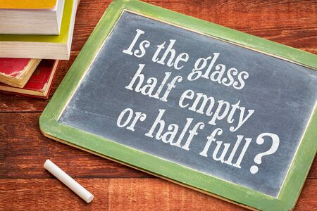 Is the glass half empty or half full question on a slate blackboard with a white chalk and a stack of books against rustic wooden table Stock fotó