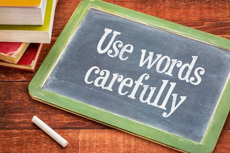 carefully: Use words carefully - text on a  slate blackboard with a white chalk and a stack of books against rustic wooden table