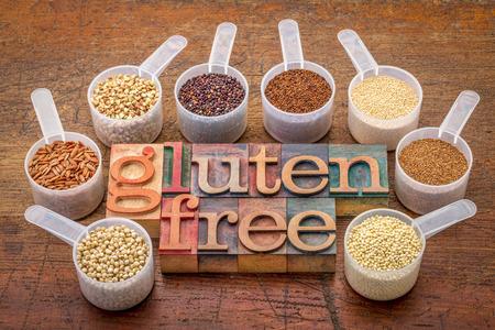 gluten free grains (quinoa, brown rice, kaniwa, amaranth, sorghum, millet, buckwheat, teff) - measuring scoops with a text in letterpress wood type Standard-Bild