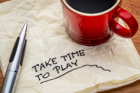 work life balance: Take time to play advice on a napkin with a cup of coffee - work life balance concept Stock Photo