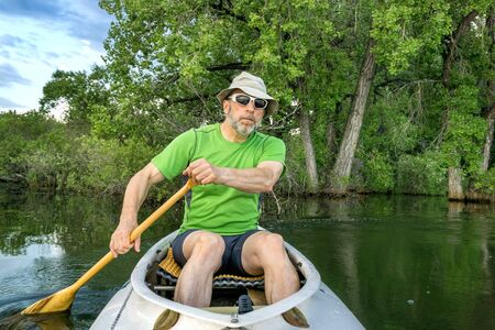 paddler: senior male paddler in a decked expedition canoe on a calm lake against background of trees Stock Photo