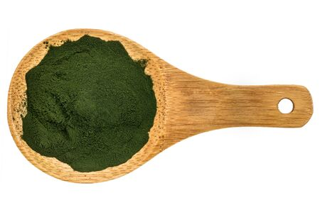 Nutrient-rich organic spirulina powder on a wooden spoon, isolated on white, top view Stock Photo