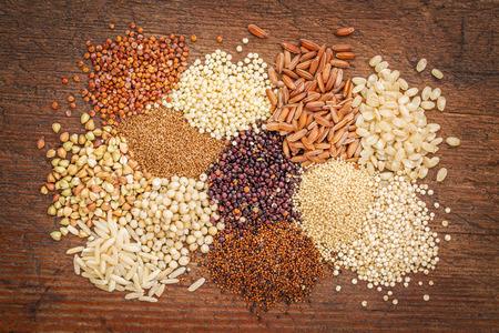 arroz blanco: gluten granos libres (trigo sarraceno, amaranto, arroz integral, mijo, sorgo, teff, quinua rojo, negro y blanco) en la madera rústica - vista desde arriba