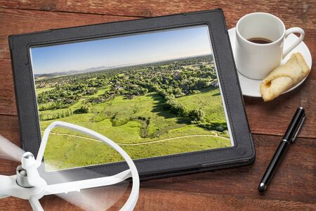 rotor: aerial photography concept - reviewing aerial pictures of Fort Collins downtown on a digital tablet with a drone rotor and coffee, screen picture copyright by the photographer