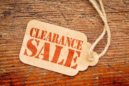 clearance sale: clearance sale sign a paper price tag against rustic red painted barn wood Stock Photo