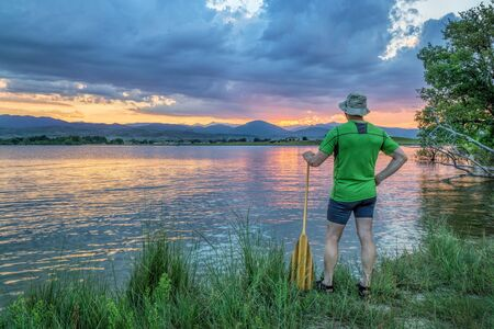 loveland: canoe paddler watching sunset over Rocky Mountains from a lake shore in Colorado near Loveland Stock Photo