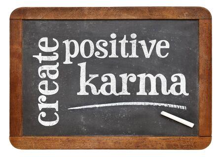vibrations: create positive karma - motivational text on a vintage slate blackboard