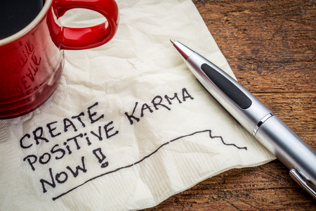 vibrations: create positive karma now - motivational handwriting on a napkin with cup of coffee