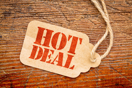 tag: hot deal sign a paper price tag against rustic red painted barn wood Stock Photo