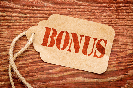 bonus: bonus sign a paper price tag against rustic red painted barn wood - shopping concept