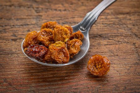superfruit: dried goldenberries on a  tablespoon against rustic scratched wood Stock Photo
