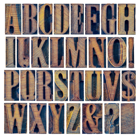 alphabet in modern letterpress wood type printing blocks, a collage of 26 isolated letters, question mark, exclamation point, ampersand and dollar sign Stock Photo