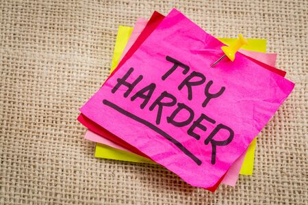 harder: try harder - motivation words on a  purple sticky note against burlap canvas Stock Photo