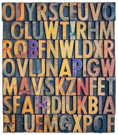 antique: background of antique letterpress wood type printing blocks, random letters of alphabet and punctuation stained by color inks, isolated on white