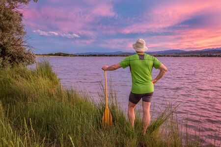 loveland: male canoe paddler watching pink sunset sky over a lake and Front Range of Rocky Mountains