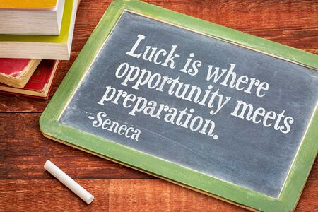 seneca: Luck is where opportunity meets preparation - Seneca quote on a slate blackboard with a white chalk and a stack of books against rustic wooden table Stock Photo