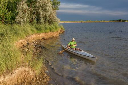 paddler: male paddler paddling a decked expedition canoe on a lake in northern Colorado Stock Photo