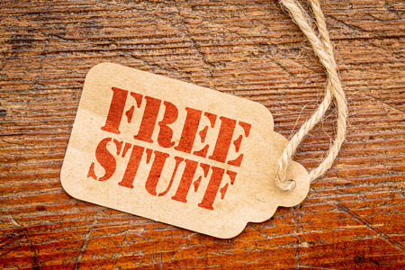 free stuff sign - a paper price tag against rustic red painted barn wood