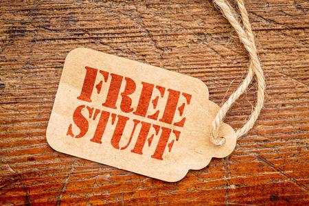 gratis spullen ondertekenen - een papieren prijskaartje tegen rustieke rode geschilderde schuur hout Stockfoto