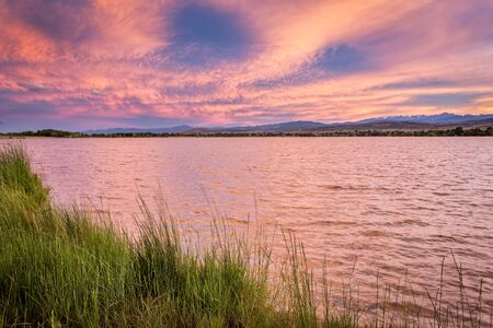 loveland: pink sunset cloudscape over a lake at foothills of Rocky Mountains in Colorado