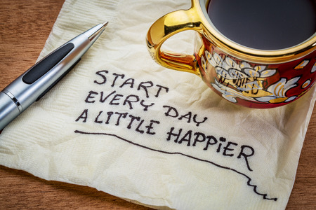 happier: Start every day a little happier - happiness and attitude concept - handwriting on a napkin with cup of coffee
