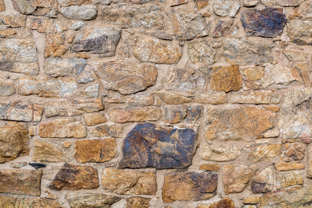 stones: background and texture of old stone wall built with irregular sandstone blocks