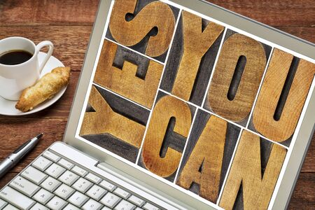 printing block block: Yes you can - motivational slogan - a  text in vintage letterpress wood type printing block on a laptop screen with a cup of coffee