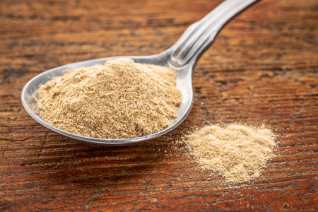 maca root: maca root powder on a tablespoon against rustic wood - superfood supplement concept