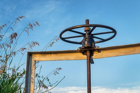 winch of irrigation ditch gate against sky with tall grass