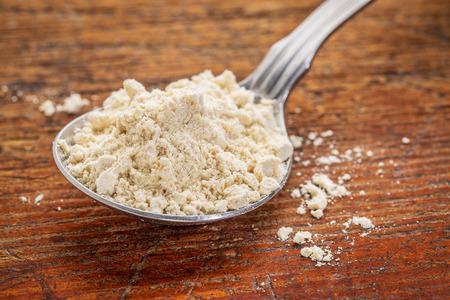 flour: cucharada de harina de gluten de quinua libre contra la madera rústica Foto de archivo